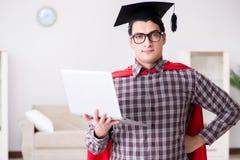 Die tragende Doktorhut des Superheld-Studenten und Halten eines Laptops Lizenzfreies Stockfoto