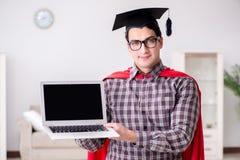 Die tragende Doktorhut des Superheld-Studenten und Halten eines Laptops Lizenzfreie Stockfotografie