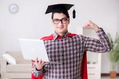 Die tragende Doktorhut des Superheld-Studenten und Halten eines Laptops Lizenzfreie Stockbilder