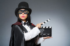 Die tragende Maske der Frau mit Filmbrett Stockfotografie