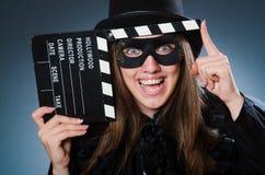 Die tragende Maske der Frau mit Filmbrett Stockfoto