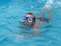 Die tragenden Schauspiele des Jungen für das Schwimmen schwimmt im Pool Lizenzfreies Stockbild