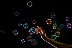 Die transparenten, schillernden Seifenblasen lokalisiert auf Schwarzem lizenzfreie stockbilder
