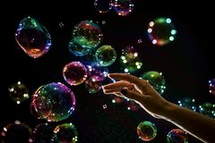 Die transparenten, schillernden Seifenblasen lokalisiert auf Schwarzem lizenzfreie stockfotos