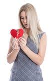 Die traurige blonde kaukasische Frau, die gebrochenes rotes Herz hält - lieben Sie sickne Lizenzfreie Stockfotos