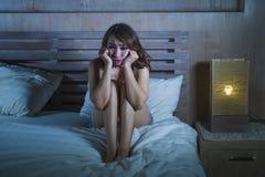 Die traurige deprimierte lateinische Frau, die auf dem Bettdenken sitzt, sorgte sich ungefähr Lizenzfreie Stockfotografie