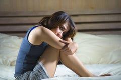 Die traurige deprimierte lateinische Frau, die auf dem Bettdenken sitzt, sorgte sich ungefähr Lizenzfreie Stockbilder