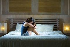 Die traurige deprimierte lateinische Frau, die auf dem Bettdenken sitzt, sorgte sich ungefähr Stockbilder