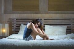 Die traurige deprimierte lateinische Frau, die auf dem Bettdenken sitzt, sorgte sich ungefähr Lizenzfreies Stockfoto