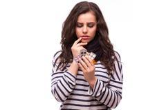 Die traurige junge Frau, die Grippe hat, nimmt Pillen ein Stockfoto