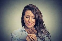 Die traurige junge Frau ermüdete von den Diätbeschränkungen Bonbonschokolade sehnend Stockfotos