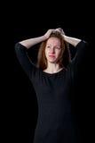 Die traurigen jungen Frauen brünieren Haar schreiend auf einem schwarzen Hintergrund Stockbild