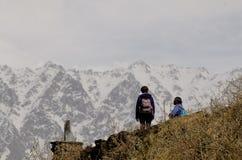 Die Trekkers, die Panoramablick des Schnees aufpassen, bedeckten Berge lizenzfreie stockbilder