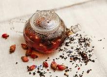 Die trockenen roten kleinen Rosen mit schwarzem Tee in der Glas- Teekanne, Tee trinkend, aromatisierte Blumen, raues Leinen-Table Lizenzfreie Stockfotografie