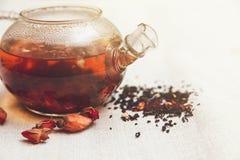 Die trockenen roten kleinen Rosen mit schwarzem Tee in der Glas- Teekanne, Tee trinkend, aromatisierte Blumen, verlegen raues Lei Lizenzfreies Stockfoto