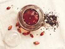 Die trockenen roten kleinen Rosen mit schwarzem Tee in der Glas- Teekanne, Tee trinkend, aromatisierte Blumen, verlegen raues Lei Stockbilder