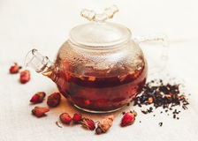 Die trockenen roten kleinen Rosen mit schwarzem Tee in der Glasteekanne Lizenzfreie Stockfotos