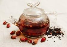 Die trockenen roten kleinen Rosen mit schwarzem Tee in der Glasteekanne, Tee trinkend, aromatisierte Blumen, verlegen rauen Leine Lizenzfreie Stockfotos