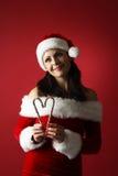 Die träumerische Frau, die Weihnachtsmann trägt, kleidet das Halten des Zuckerstange-Formherzens auf rotem Hintergrund Stockbild