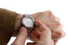 Die Uhr der Zeit an Hand schauen Stockbilder