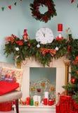 Die Uhr zeigt bei fünf Minuten bis zwölf im Kamin, verziert zum neuen Jahr Stockbild