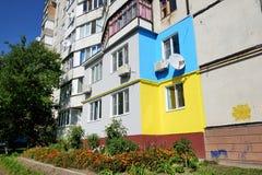 Die ukrainischen Leute malten ihre Häuser in den Farben der ukrainischen Flagge Stockbild