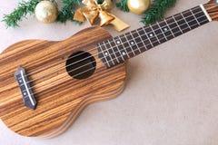 Die Ukulele auf dem Holztisch mit Weihnachtsdekoration Lizenzfreie Stockfotos