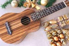 Die Ukulele auf dem Holztisch mit Weihnachtsdekorationssatz Stockfotografie