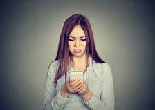Die umgekippte Frau, die Mobiltelefon betrachtet, missfiel mit Mitteilung, die sie empfing lizenzfreies stockbild