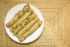 Die umsponnenen Pfannkuchen auf Platte Stockfotos