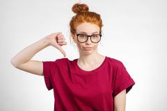 Die unglückliche Frau, die Daumen gestikulieren gibt unten, das Schauen mit negativem Ausdruck Stockbild