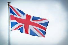Die Union Jack-Flagge des Vereinigten Königreichs brennt im Wind durch Stockbild