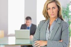Die Unsmiling Geschäftsfrau, die Kamera betrachtet, kreuzte Arme mit einem BU Stockfotos