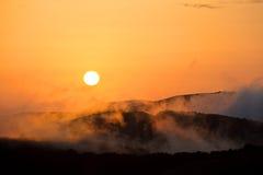 Die untergehende Sonne in den Bergen mit Abendnebel Stockbild