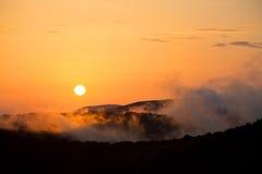 Die untergehende Sonne in den Bergen mit Abendnebel Lizenzfreie Stockfotos