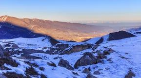 Die untergehende Sonne in den Schnee-mit einer Kappe bedeckten Bergen Stockbild