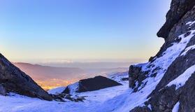 Die untergehende Sonne in den Schnee-mit einer Kappe bedeckten Bergen Lizenzfreie Stockbilder