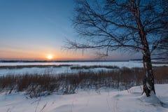 Die untergehende Sonne an einem eisigen Abend Stockbild