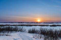 Die untergehende Sonne an einem eisigen Abend Lizenzfreie Stockfotografie