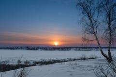 Die untergehende Sonne an einem eisigen Abend Lizenzfreie Stockfotos
