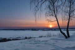 Die untergehende Sonne an einem eisigen Abend Stockfoto