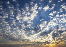 Die untergehende Sonne hinter den überschreitenen Wolken stockfoto