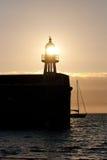 Die untergehende Sonne scheint durch einen Leuchtturm auf einem Hafen Erin Harbour stockbild