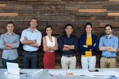 Die Unternehmensleiter, die mit den Armen stehen, kreuzten im Büro stockfoto