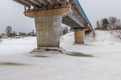 Die Unterstützungen der Brücke über dem Fluss Mologa Winter Eis Stockfotografie