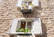 Die ursprünglichen hölzernen Fensterläden auf Steinwand in altem Budva, Montenegro Lizenzfreies Stockfoto