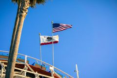 Die USA-Flagge und die Kalifornien-Republik kennzeichnen den Schlag im Wind auf eine Achterbahn Lizenzfreie Stockfotografie