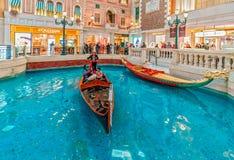 Die venetianische Macao-Urlaubshotelinnenraumansicht Gondoliere reitet chinesische Touristen in der Gondel Stockbild