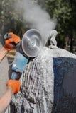 Die Verarbeitung des wilden Steingabbrogranits mit einem Winkelschleifer, der Bildhauer schafft ein Meisterwerk stockfotografie