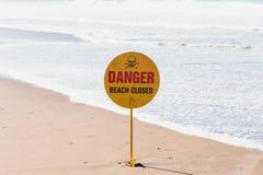 Die verbotene Schwimmen, setzen geschlossenes Warnzeichen auf einem Strand mit blauem bewölktem Himmel und sandigem Strand im Hin Stockbild